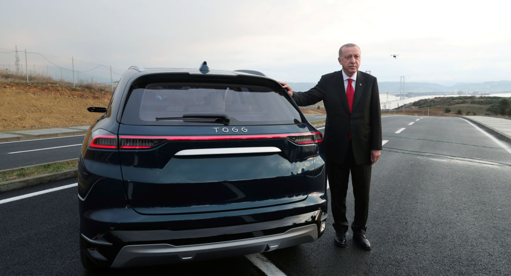 Turkish President Tayyip Erdogan poses with a prototype of the domestic electric car project in Gebze, Turkey, 27 December 2019.