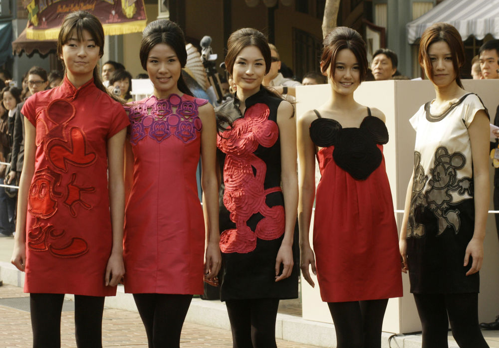 Models at Disneyland Hong Kong showing off Minnie Mouse-themed dresses.