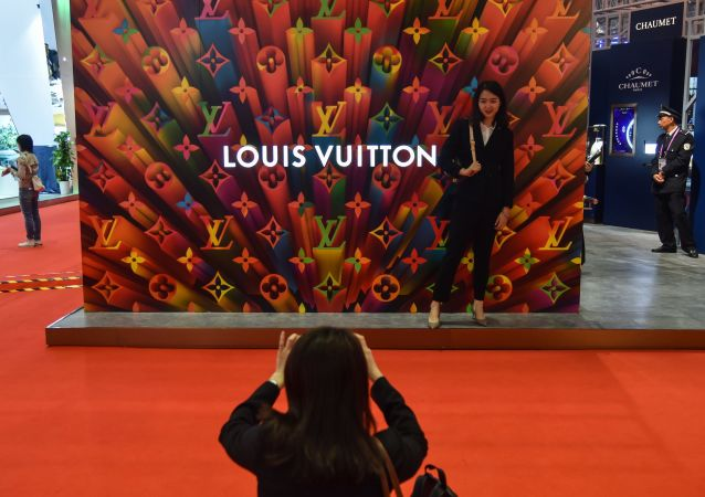 A woman poses for a picture next to a Louis Vuitton stand during the second China International Import Expo in Shanghai on november 6, 2019.