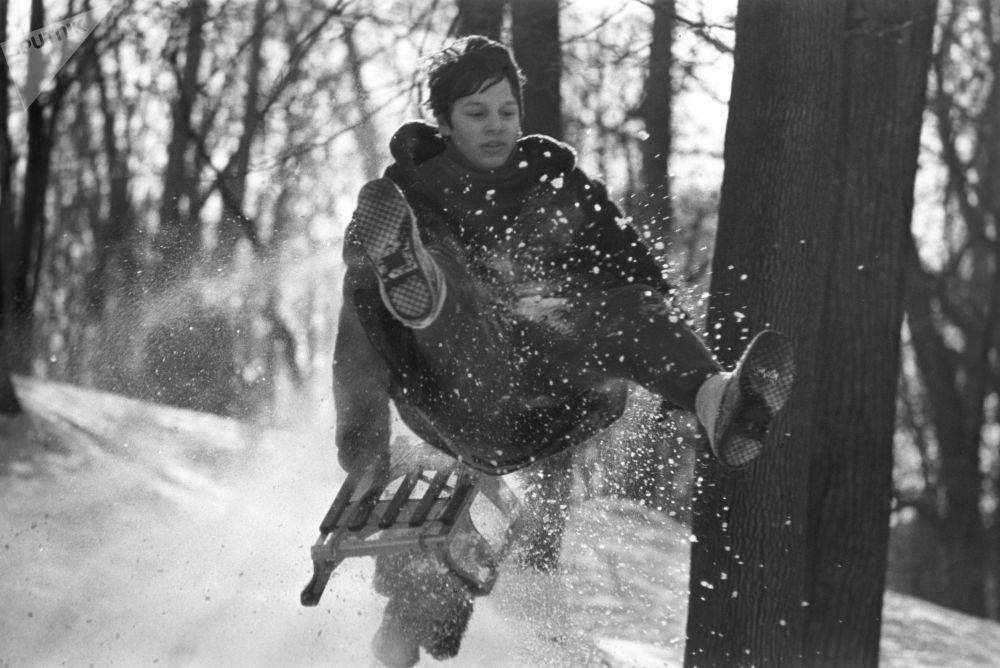 A boy enjoys a sledge ride in 1976