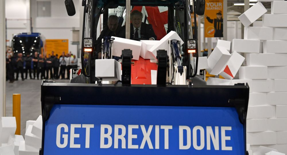 Britain's Prime Minister and Conservative party leader Boris Johnson drives a Union flag-themed JCB, with the words Get Brexit Done inside the digger bucket, through a fake wall emblazoned with the word GRIDLOCK, during a general election campaign event at JCB construction company in Uttoxeter, Staffordshire, on December 10, 2019.