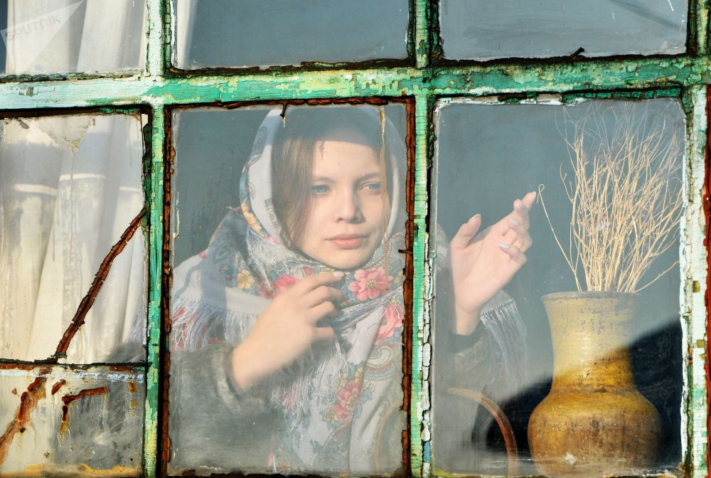 A girl looks out of the window during Christmas fortune-telling in the village of Chernorechye in the Chelyabinsk region.