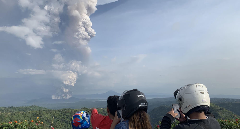 People take photos of a phreatic explosion from the Taal volcano as seen from the town of Tagaytay in Cavite province, southwest of Manila, on January 12, 2020.