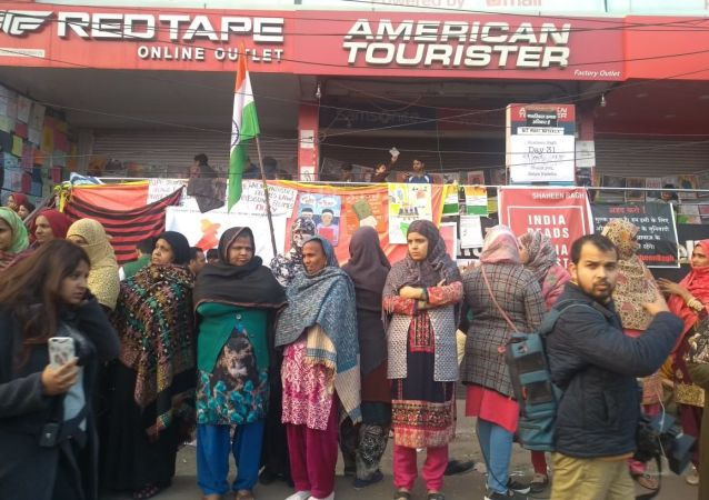 Women protesters holding national flag line up in front of anti-CAA and NRC posters drawn by children