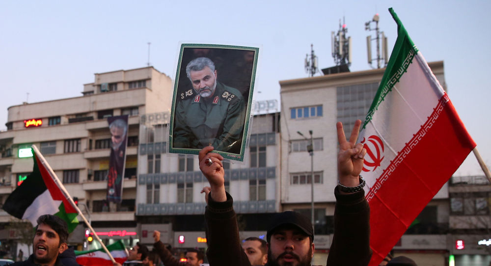 A man holds a picture of late Iranian Major-General Qassem Soleimani, as people celebrate in the street after Iran launched missiles at U.S.-led forces in Iraq, in Tehran, Iran