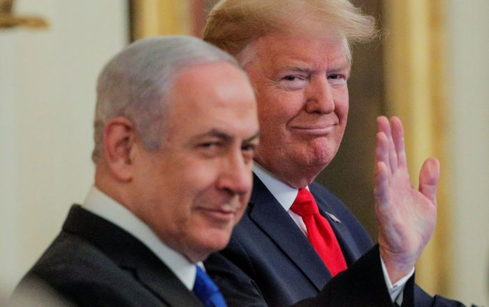 U.S. President Donald Trump waves next to Israel's Prime Minister Benjamin Netanyahu prior to announcing his Middle East peace plan proposal in the East Room of the White House in Washington, U.S., January 28, 2020. REUTERS/Brendan McDermid