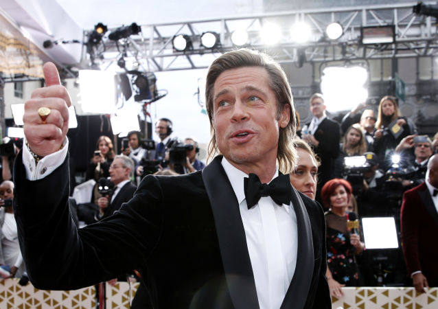 Brad Pitt gestures as he poses on the red carpet during the Oscars arrivals at the 92nd Academy Awards in Hollywood, Los Angeles, California, U.S., February 9, 2020