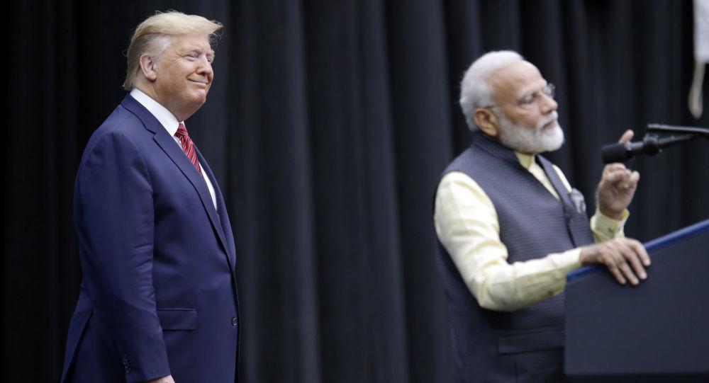 President Donald Trump listens as India Prime Minister Narendra Modi introduces him