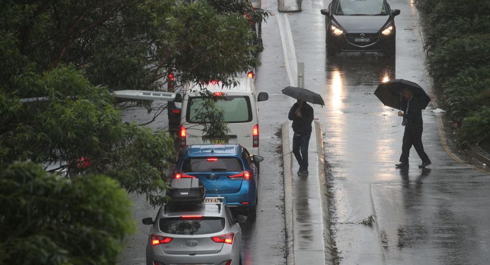 Pedestrians brave strong wind and rain in Sydney, New South Wales, Australia, February 9, 2020.  REUTERS/Loren Elliott