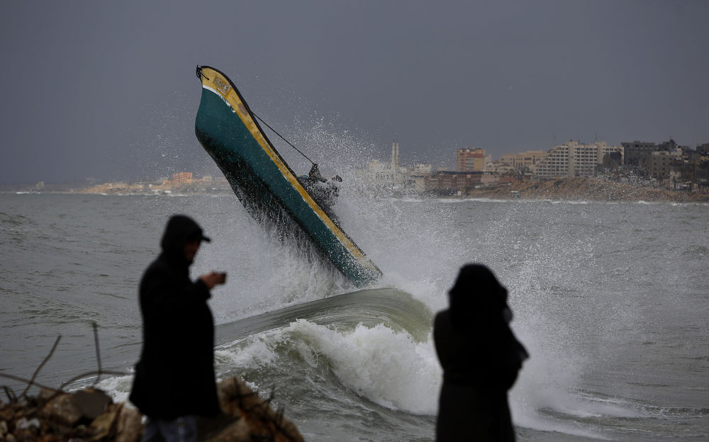 Palestinian fishermen ride their boat amid high waves on a windy and rainy day at the sea in Gaza City, Sunday, Feb. 9, 2020.