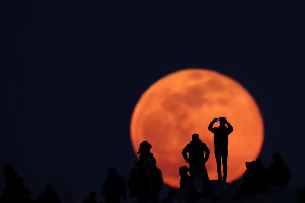 People observe a rising full snow moon as they visit the Areios Pagos hill at the archaeological site of the Acropolis in Athens, Greece, February 9, 2020.