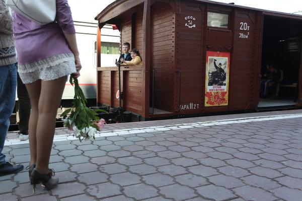 Молодые люди стоят у ретро-поезда Победа в Волгограде