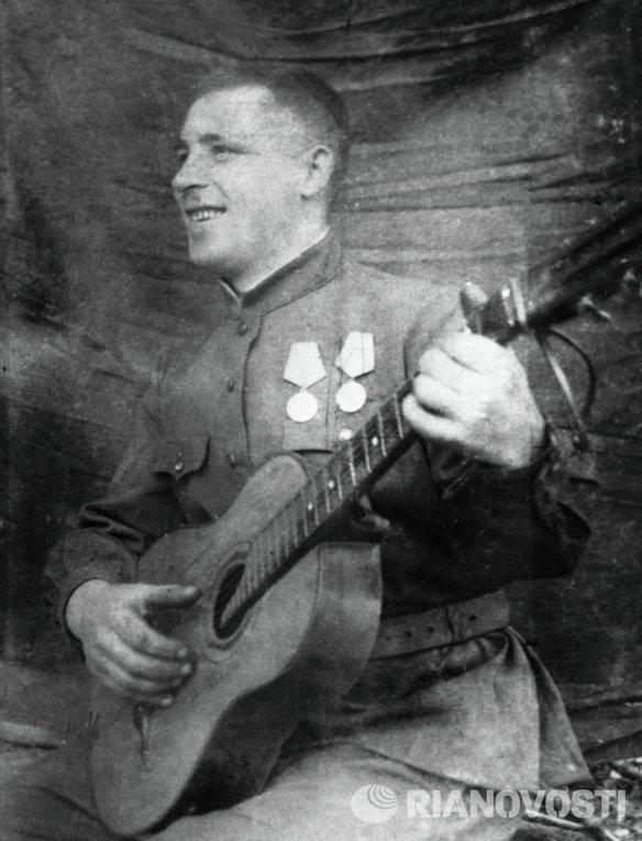Участник событий на Курской дуге играет на гитаре в перерыве между боями