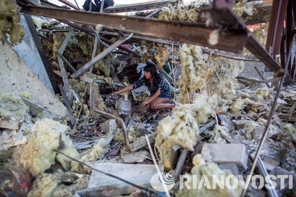 Девушка разбирает завалы в продуктовом магазине, который был разрушен прямым попаданием мины во время артобстрела украинскими силовиками города Краматорска.
