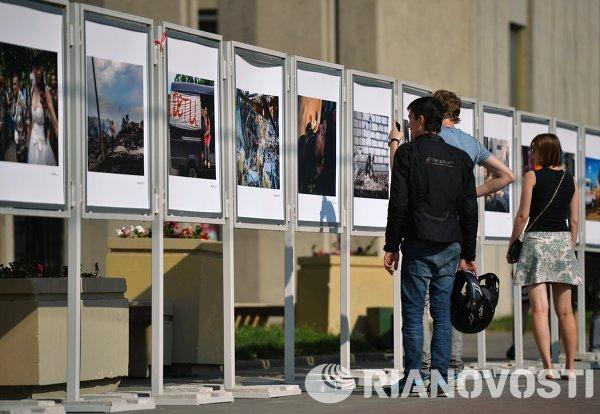 Прохожие рассматривают выставку работ фотокорреспондента Андрея Cтенина