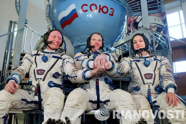 Члены дублирующего экипажа МКС-39/40 - астронавт НАСА Барри Уилмор, космонавты Александр Самокутяев (слева направо) и Елена Серова на тренажере транспортного пилотируемого корабля Союз ТМА-М в Центре подготовки космонавтов имени Ю.А. Гагарина в Звездном городке